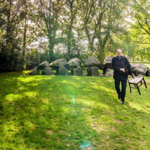 Peter Hendriks van Uitvaartzorg BijZonder met een lege stoel bij de Hunebedden in Rolde